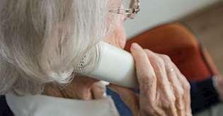 Äldre kvinna med grått hår som håller i en telefonlur.