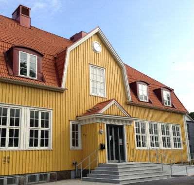 Den gula träfasaden på Rävlanda bibliotek.