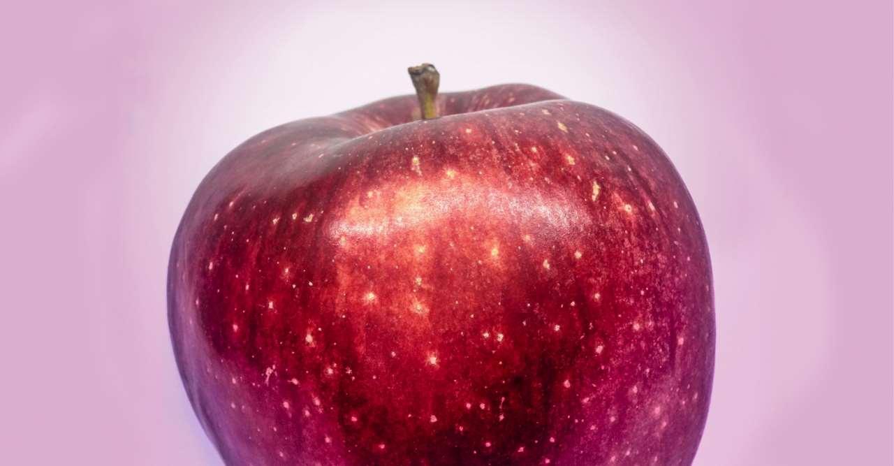 Rött äpple mot en rosa bakgrund.