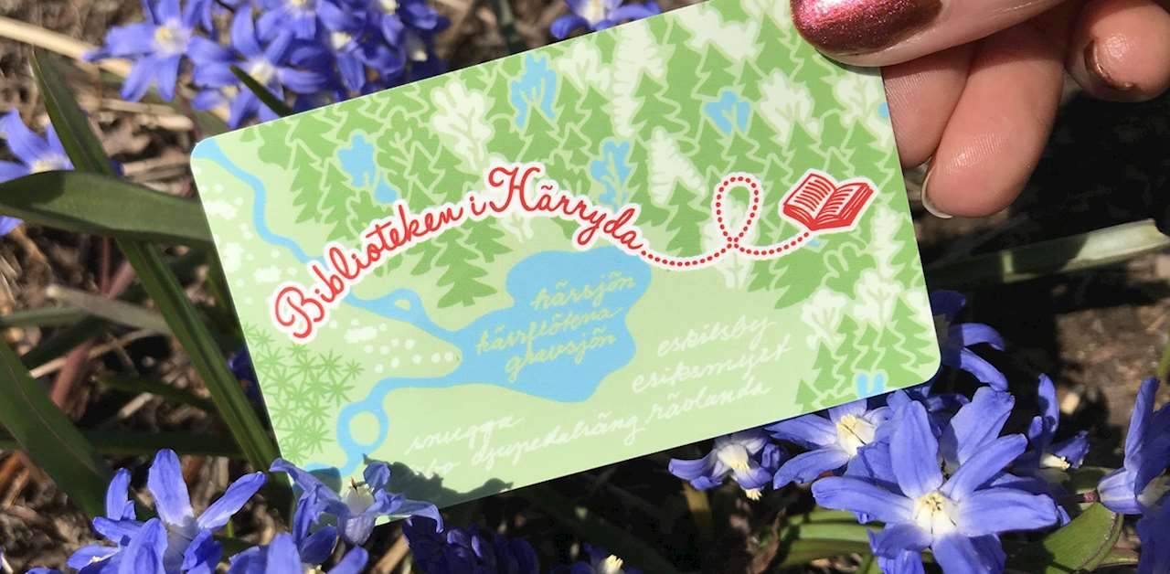 """Hand som håller i ett bibliotekskort med röd slingrig text """"Biblioteken i Härryda"""" mot en blå och grön skogsbakgrund."""